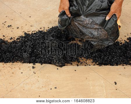 Human hand pouring asphalt for repairing the road