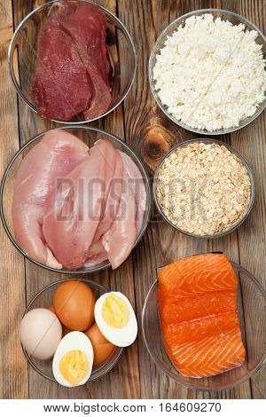 Protein diet, fish, cheese, eggs, meat and chicken wooden background
