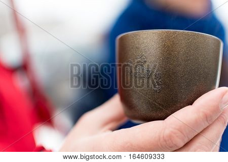 Hand holding a team cup with Chinese symbols on it