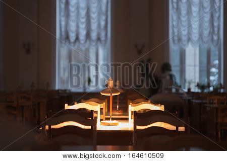 Reading at the table with a lamp in the library.