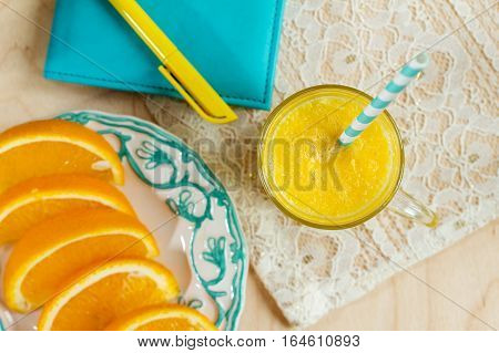 Plate with slices of oranges and orange juice. Phonebook with pencil and fresh orange juice. Focus on the glass.