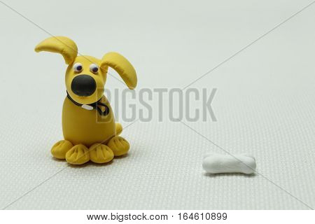 Toy of a dog from plasticine and a bone on a light background