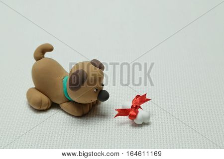 Toy of a dog from plasticine and a bone tied up by a band on a light background