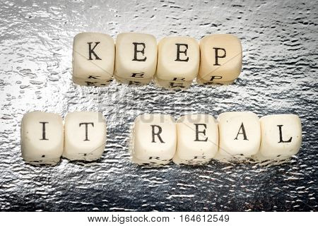 Keep It Real Text On A Wooden Cubes On A Shiny Silver Background