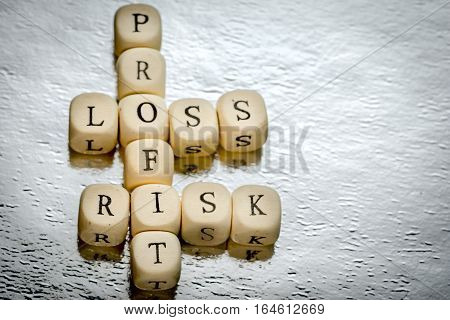 Profit Loss Risk Crossword On A Wooden Cubes On A Shiny Silver Background