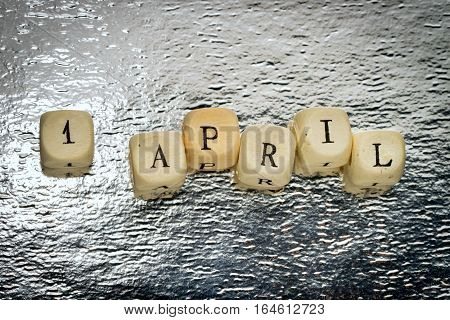 1 april text on a wooden cubes on a shiny silver background