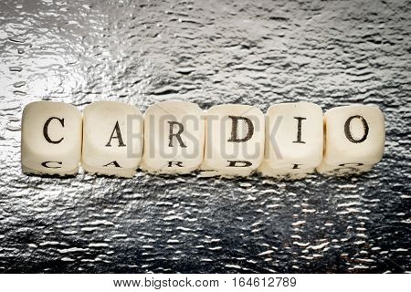 Cardio word with the letters straight in a row on a wooden cubes on a shiny silver background
