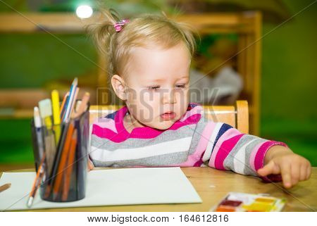 Adorable child girl drawing with colorful pencils in nursery room. Kid in kindergarten in Montessori preschool class.
