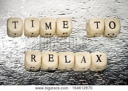 Time To Relax Text On A Wooden Cubes On A Shiny Silver Background