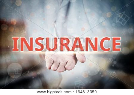 Man Hand Holding Insurance Text On Blurry Home Icon Property Background.