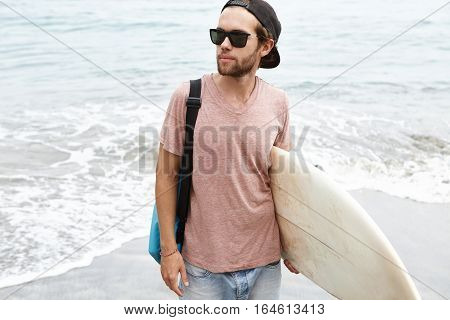 Outdoor Shot Of Fashionable Young Male Model Wearing Black Shades And Snapback Carrying White Surfbo