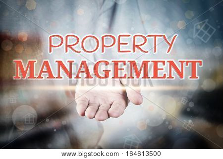 Man Hand Holding Property Management Text On Blurry Home Icon Property Background.