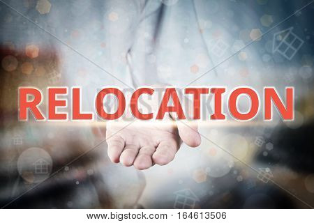 Man Hand Holding Relocation Text On Blurry Home Icon Property Background.
