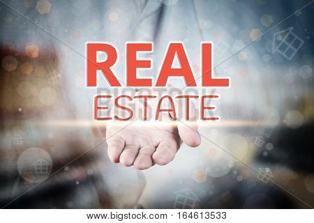 Man Hand Holding Real Estate Text On Blurry Home Icon Property Background.
