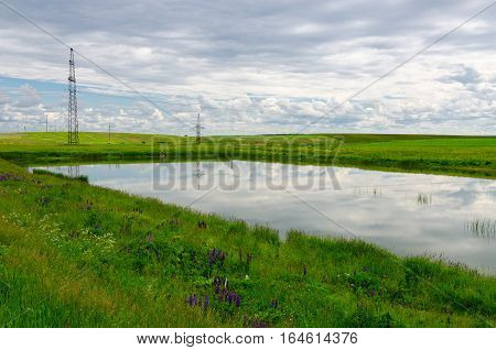Small pond surrounded by green fields supporting pillars of high-voltage power line along road rural landscape