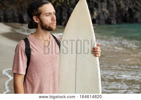 Outdoor Shot Of Attractive Bearded Surfer Holding His White Surfboard Standing On Beach And Looking