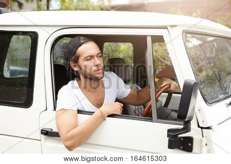 Close Up Of Attractive Young Man With Beard Sitting In His White Vehicle In Search For Extreme Durin