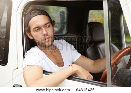 Fashionable Young Man Wearing Snapback Backwards Driving His Sport Utility Vehicle And Sticking His