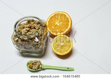 Healty food with bowel and spoon of cereals. Orange and lemon are next to cut in half iIsolated on white background.