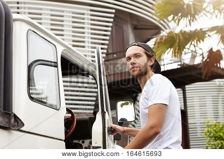 Fashionable Young Caucasian Male Student Wearing Snapback Opening Door Of His White Four-wheel Drive