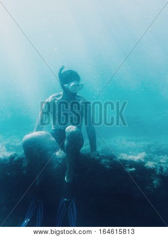 Underwater image of young man free diver sitting on reef