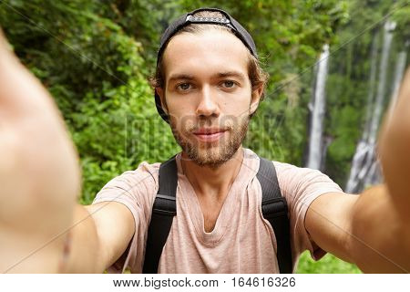 Cheerful Young Bearded Hipster Wearing Baseball Cap Holding Camera With Both Hands And Recording Vid