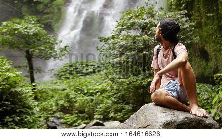 Outdoor Shot Of Stylish Young Caucasian Hiker Sitting Barefooted On Big Rock And Looking Over His Sh