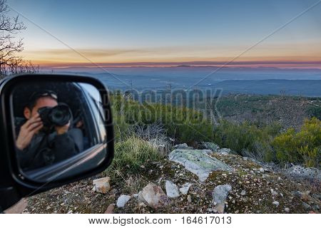 Wide angle view of landscape with blurred tourist reflected in mirror taking photos inside 4x4
