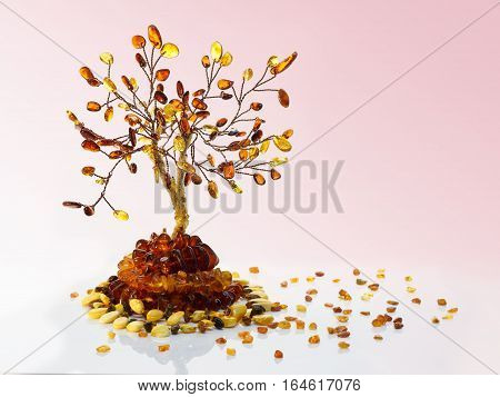 Decorative tree made with yellow and dark brown baltic amber amber beads and small pieces of raw amber on white acrylic surface on pink gradient background