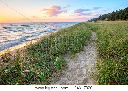 A Walk On The Beach. Sandy trail winds along a Great Lakes beach with a sunset horizon and sand dunes as a backdrop. Muskegon, Michigan