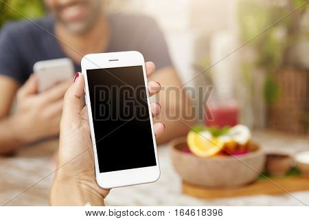 Cropped Shot Of Caucasian Woman's Hand Holding Generic Mobile Phone With Blank Copy Space Screen For