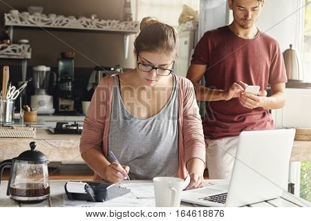 Young Beautiful Housewife Wearing Rectangular Glasses Making Necessary Calculations And Writing Down