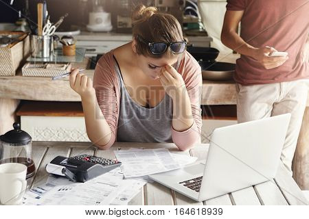 Young Family Facing Debt Problems, Can't Pay Out Their Mortgage. Stressed Woman Holding Her Head In