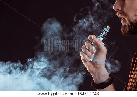 young man wearing a plaid shirt smokes an electronic cigarette on a black background. close-up