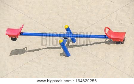 Teeter totter with red chairs beach sand balance close up outdoor playground