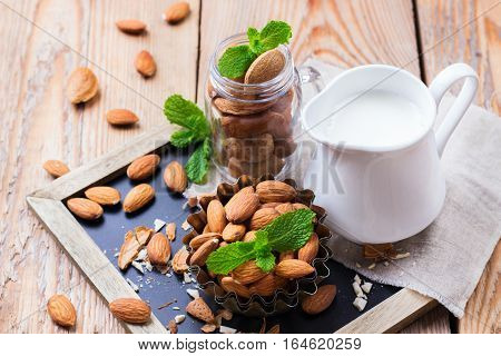 Almond milk in a jug with ingredients for healthy vegetarian vegan breakfast on a rustic wooden table
