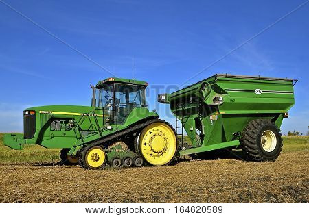 SHELDON, NORTH DAKOTA, September 29, 2016 : The 8400T tractor with tracks pulling a grain cart in the stubble of a wheat field is a product of John Deere Co, an American corporation that manufactures agricultural, construction, forestry machinery, diesel