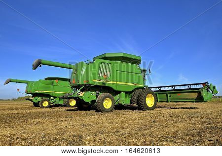 SHELDON, NORTH DAKOTA, September 29, 2016 : The green self propelled combines in the autumn residue of a soybean field are products of John Deere Co, an American corporation that manufactures agricultural, construction, forestry machinery, diesel engines,