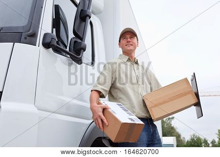 a smiling delivery person is standing next to his truck.