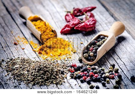 Mixed whole pepper on a wooden scoop. Natural old background. Concept of food, spice