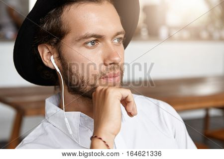 Close Up Shot Of Attractive And Stylish Man With Beard Looking Pensive, Listening To Music Online On