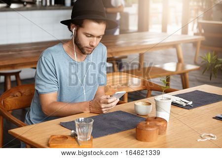 Good-looking Young Hipster Messaging Online On His Mobile Phone, Using Free Wi-fi At Cafe. Stylish B