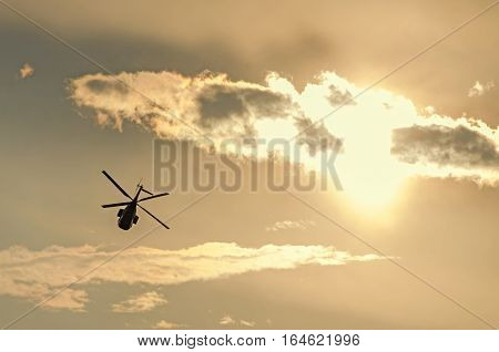 IAR Puma elicopter silhouette flying in the cloudy sky stunt aerobatic show sunset and sun rays.