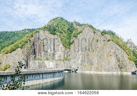 The barrage dam Vidraru on the river Arges green hills and rocks blue sky
