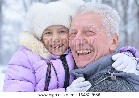 happy grandfather and granddaughter posing outdoors in winter