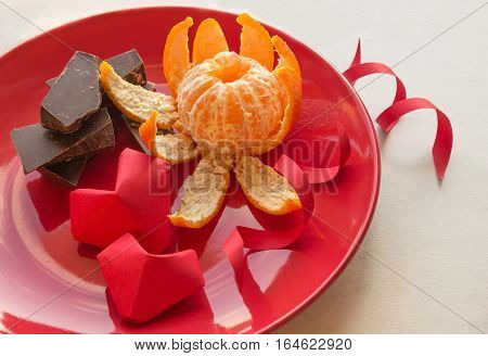 Two volumetric hearts of paper. Red plate with chocolate and mandarin in the shape of a flower. Valentine's Day. March 8. International Women's Day.