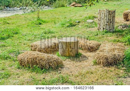 Outdoor Camp With Wooden Log Table And Straw Chairs.