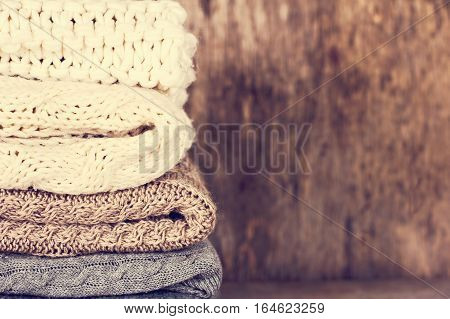 A stack of woolen sweater plaid. Warm clothing. Home atmosphere winter clothing. Gray white and brown sweater. Warm and cozy. Knitted clothes. Cozy atmosphere.