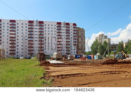 Workers tractor area with sand and grass near building on construction site at summer day