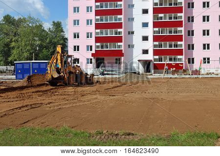 Tractor works near new building on construction site at summer day